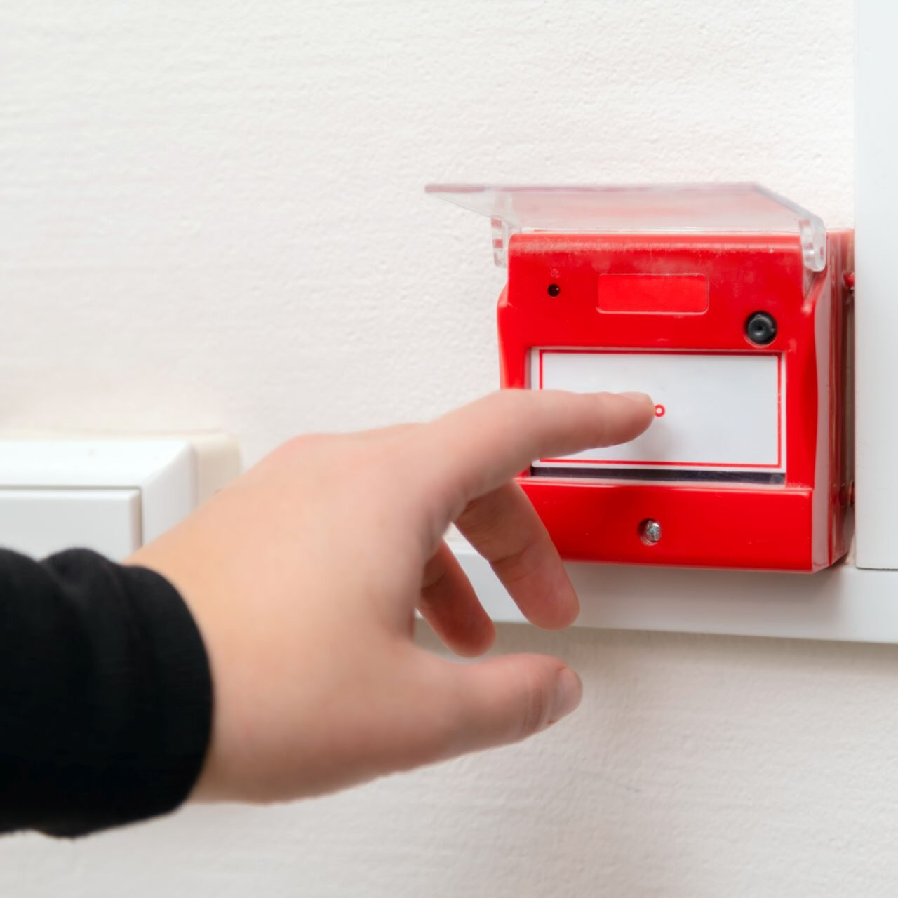 Hand pressing fire alarm button at school or business office. Close up of protection console against flame damage
