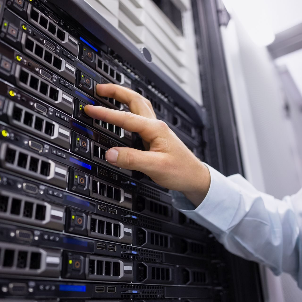 Technician working on server tower in large data center
